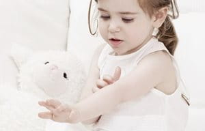 Little girl playing with stuffed animal.