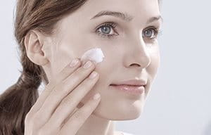 Woman is applying cream on her face.