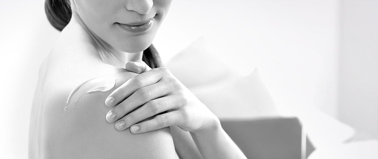 Woman applying cream on her shoulder